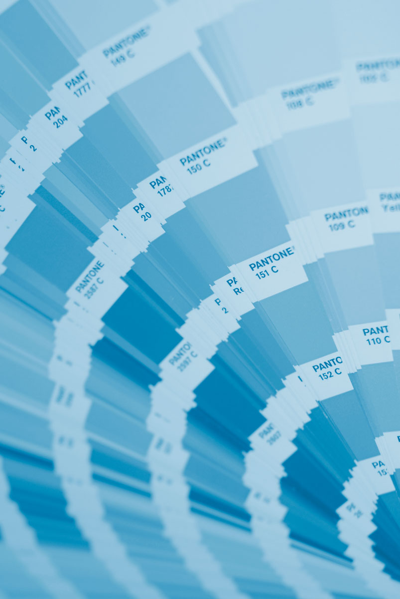 Large light blue duotone background photograph of a Pantone colour swatch book open